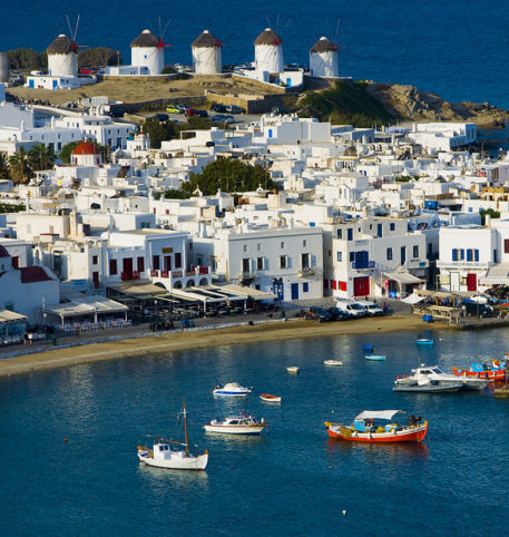Traditional windmills and whitewashed houses by the sea in Mykonos, Greece.