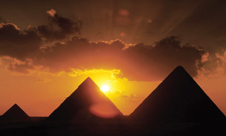 The sun sets behind the Pyramids, one of the most famous monuments in Egypt.