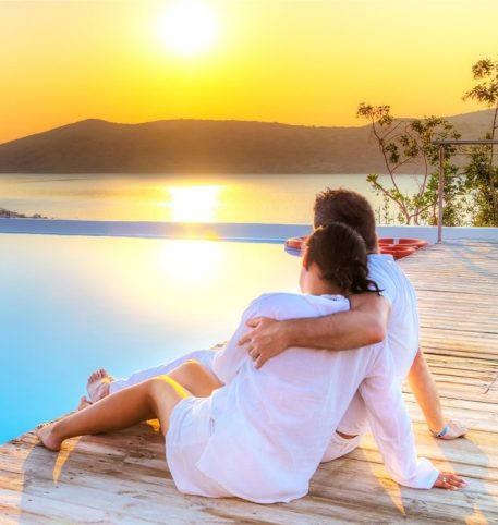 Couple sitting by the pool admiring the sea. Romantic holiday in Athens Mykonos Santorini.
