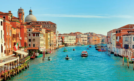 Light blue waters of a canal in Venice and little boats. Beautiful venetian buildings.