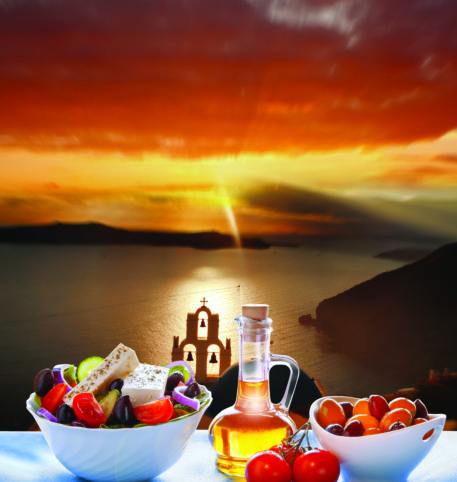 Greek salad, olive oil and a bowl with fruits on a table overlooking the Aegean sea at sunset.
