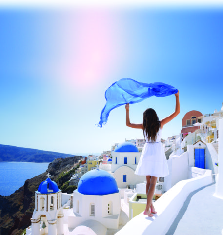 Lady by the edge of a balcony overlooking the sea in Santorini island, Greece.