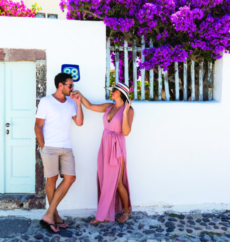 Man and woman by a white door of a luxury accommodation in a Greek island.
