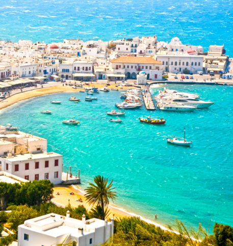 Boats in a bay and panoramic view of a village on one of the Greek islands. Crystal clear sea water.