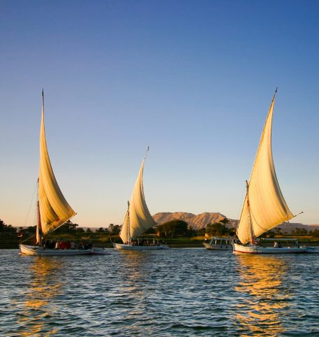 Sailing boats in the Nile River and sand dunes at the back. Egyptian Delight Egypt holidays.