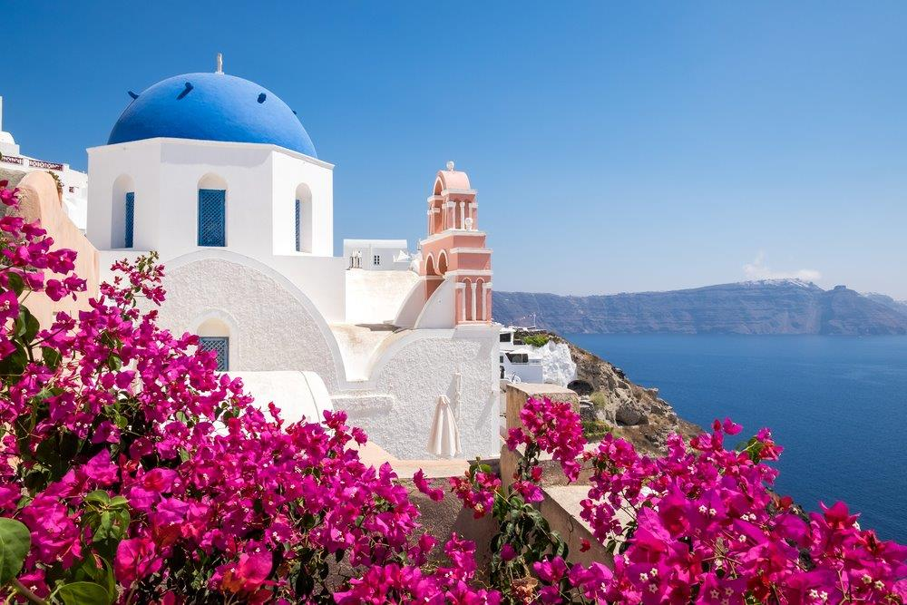 Red flowers and a whitewashed church with blue dome overlooking the sea in Santorini island.
